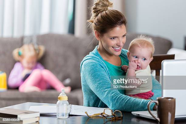 Busy mom holds daughter while working