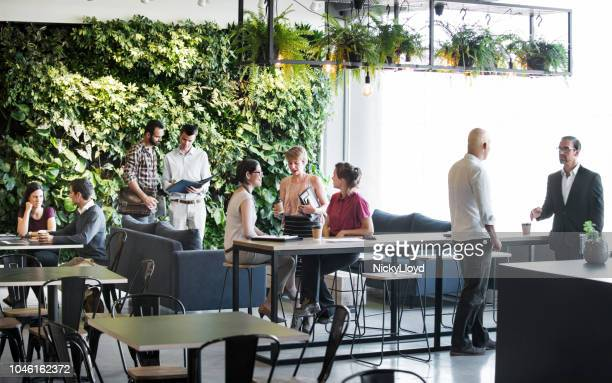 busy office common area - green color stock pictures, royalty-free photos & images