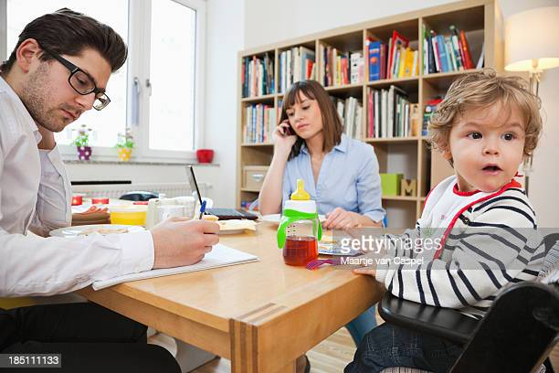 Busy parents work while the kid eats breakfast at the table