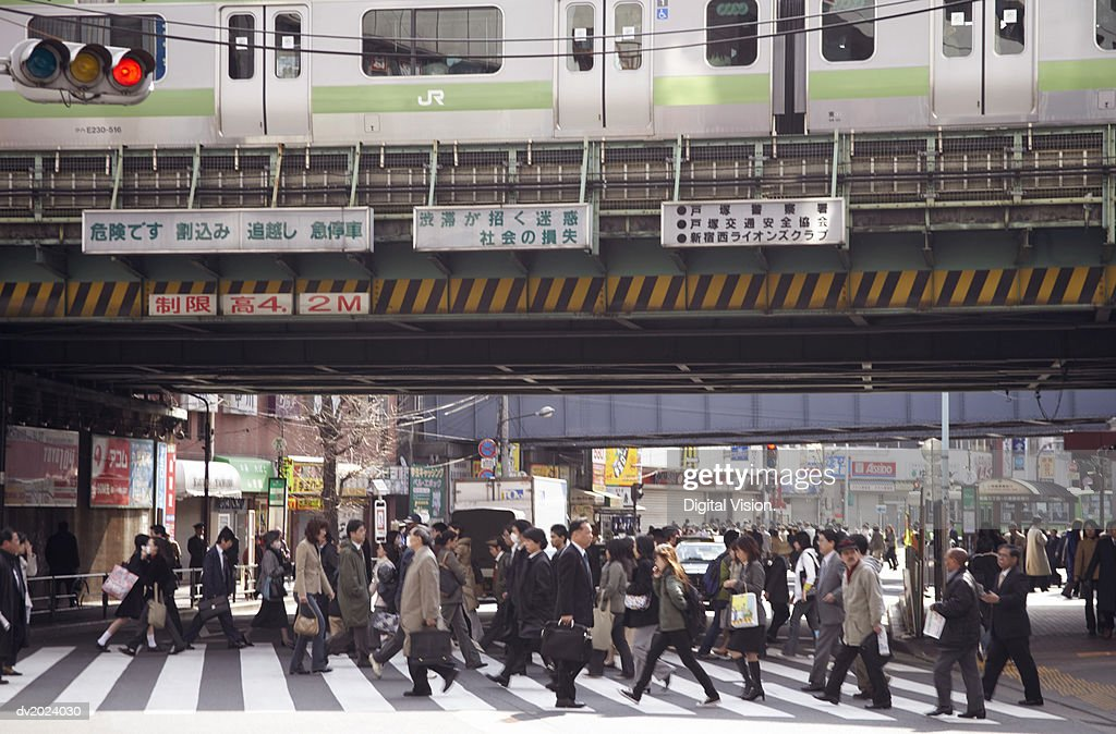 Busy Pedestrian Crossing Underneath a Railway Bridge, Japan : Stock Photo