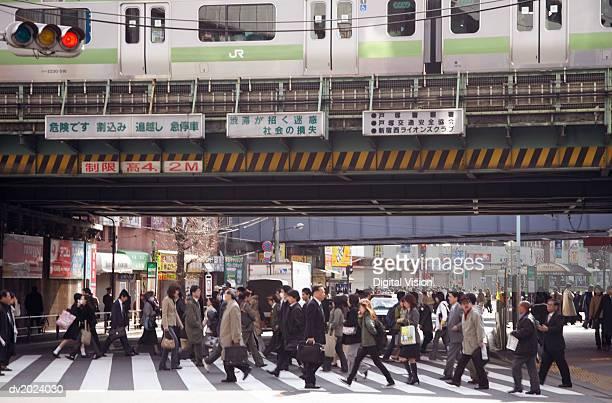 busy pedestrian crossing underneath a railway bridge, japan - 通勤 ストックフォトと画像
