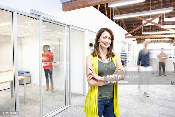 Busy people walking past businesswoman in office