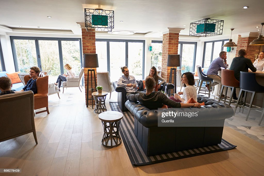 Busy Reception Area Of Modern Boutique Hotel With Guests : Stock Photo