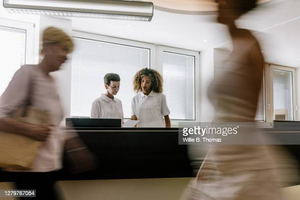 busy reception at mri clinic with patients walking by - medical receptionist uniforms stock pictures, royalty-free photos & images