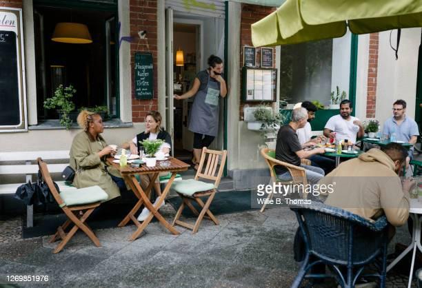 busy restaurant facade with people sitting and eating - restaurant stock-fotos und bilder