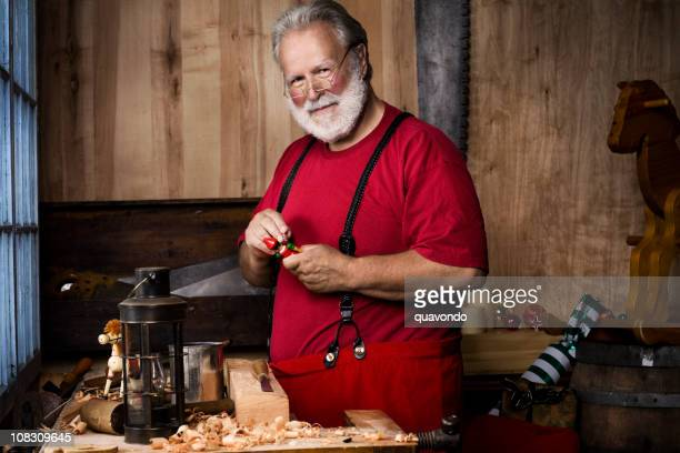 busy santa claus making toys in christmas workshop, copy space - santas workshop stock photos and pictures