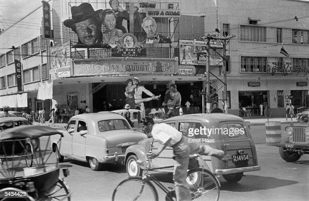 A busy street in Bangkok capital of Thailand with an American film being advertised at a cinema In black and white book