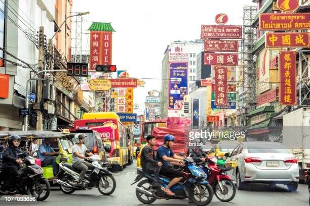 busy street in chinatown, bangkok, thailand,  with tmotorbikes, tuk.tuks and buses. - bangkok province stock pictures, royalty-free photos & images