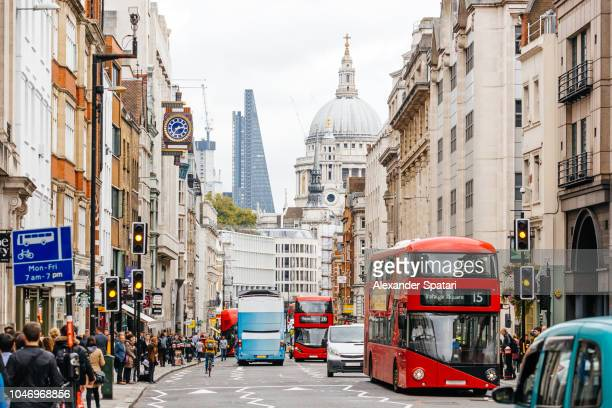busy street in city of london with heavy traffic, crowds of people and dome st. paul's cathedral - london england stock-fotos und bilder