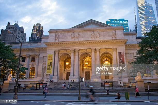 busy street in front of building entrance at dusk. - new york public library stock pictures, royalty-free photos & images