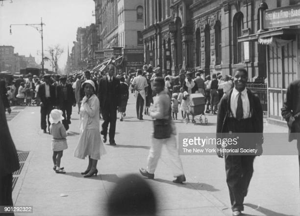 Busy street in Harlem, New York, New York, 1929. 'Free Milk Fund for Babies' at right. Possibly Lenox Avenue, looking south from just south of 130th...