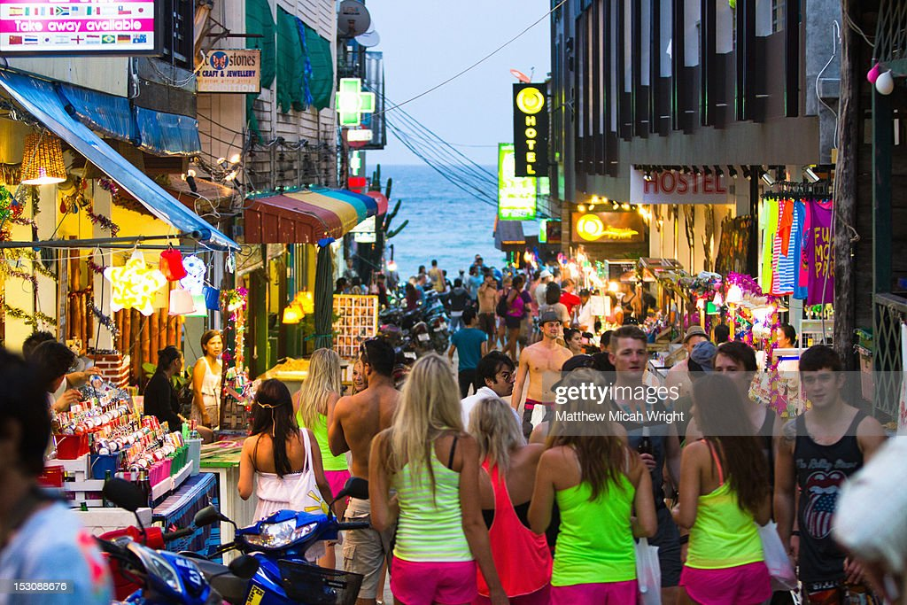 A busy street of neon clothed tourists. : Stock Photo