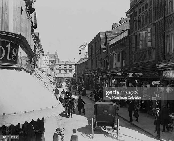 Busy street scene of Bedford High Street bustling with people and traffic England circa 1900