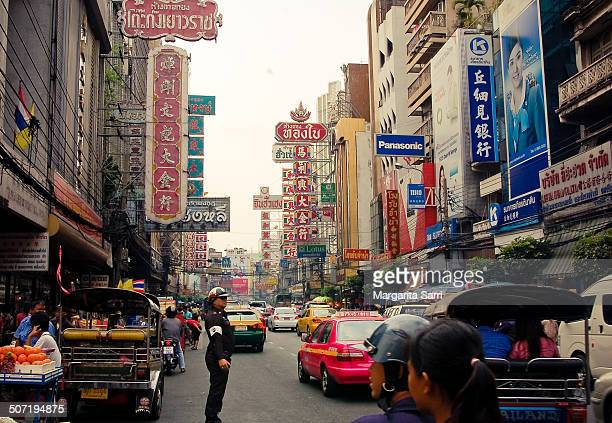 CONTENT] Busy street scene with cars and shop and advertising signs in China town Bangkok