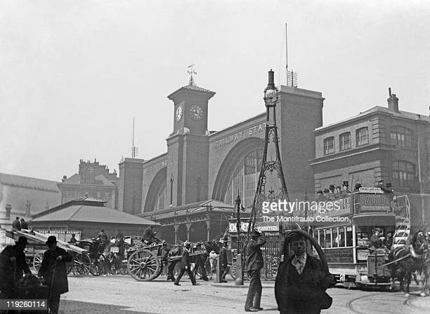 Busy street scene with people horse and carts carriages and horse drawn open topped buses outside The Great Northern Railway Station designed by...