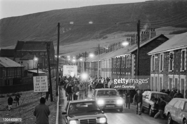 Busy street scene with striking mine workers one carrying a placard during the miners' strike picket the Maerdy Colliery one of the last working...