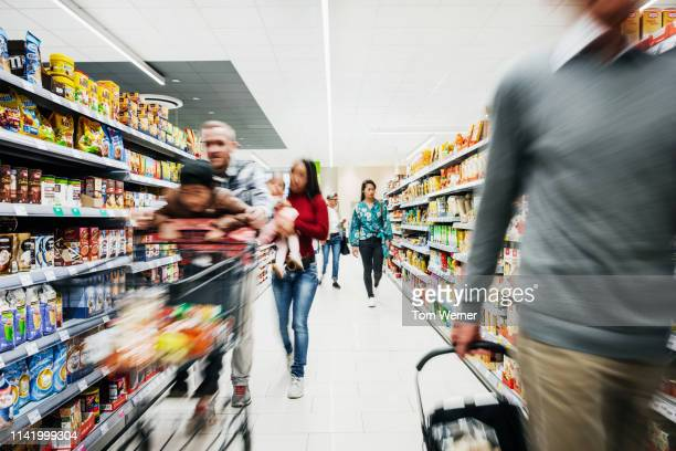 busy supermarket aisle with customers - supermarket stock pictures, royalty-free photos & images