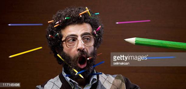 Busy teacher with beard and long hair confronting flying pencils
