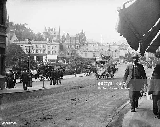A busy town centre street scene in Bournemouth a large coastal resort town on the south coast of England with lots of pedestrians horse drawn...