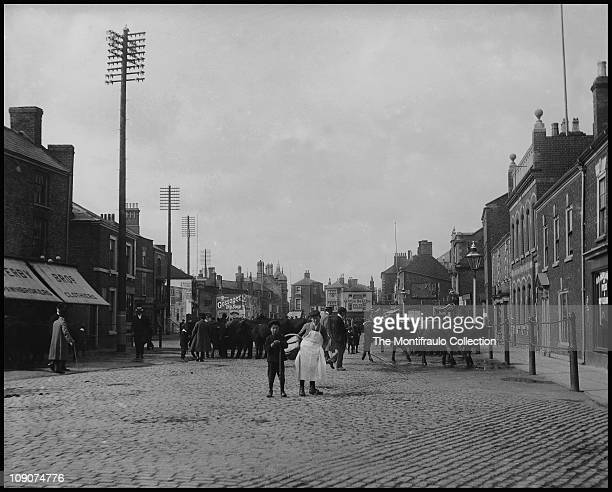 Busy town scene in Spalding England Two young working boys standing in front of a large herd of cattle on street at cattle market circa 1912