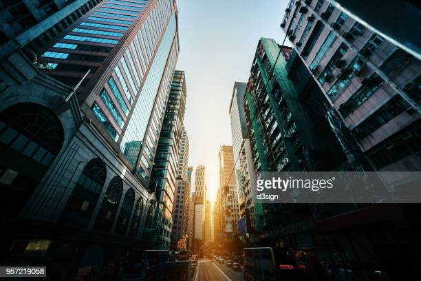 busy traffic and dense commercial skyscrapers along the road in city downtown district, hong kong at sunrise - wanchai stock photos and pictures