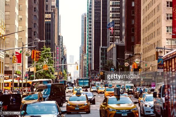 busy traffic at 6th avenue in new york city, usa - avenida fotografías e imágenes de stock