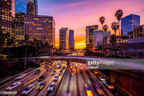 busy traffic in downtown los angeles at sunset - city of los angeles stock pictures, royalty-free photos & images