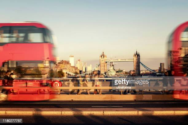 busy traffic with business people and double-decker buses on london bridge - london skyline stock pictures, royalty-free photos & images