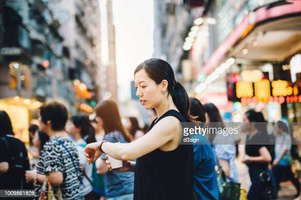 busy woman checking time on wristwatch while walking on pedestrian crossing in city, against a group of woman commuters - busy stock pictures, royalty-free photos & images
