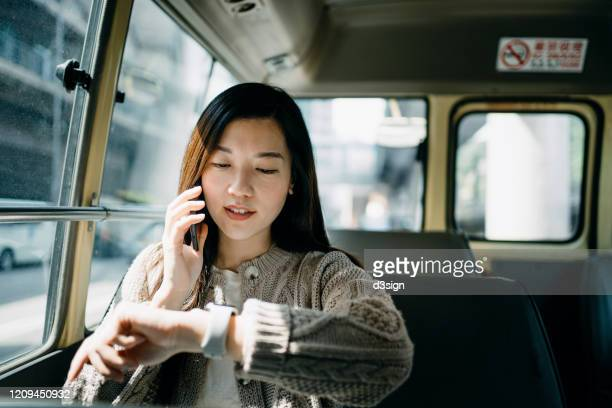 busy young asian woman talking over smartphone and checking time on smartwatch while commuting in the city riding on a minibus - urgency stock pictures, royalty-free photos & images