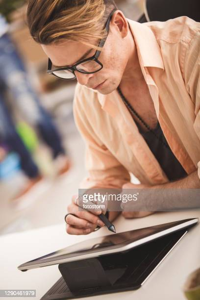 busy young entrepreneur working on his personal tablet in the office - animator stock pictures, royalty-free photos & images