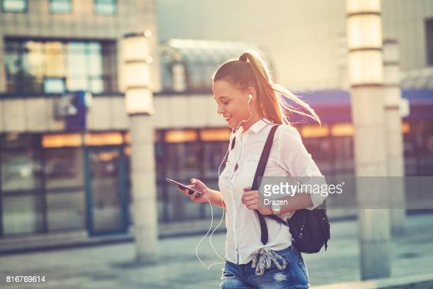 busy young woman using smart phone and listening to music - simple living stock pictures, royalty-free photos & images