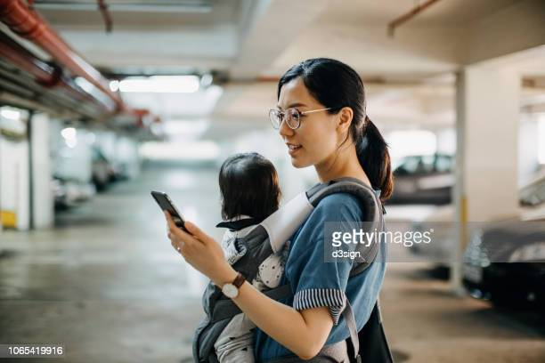 busy young woman with baby in carrier using smartphone while walking to her car in car park - homemaker stock pictures, royalty-free photos & images