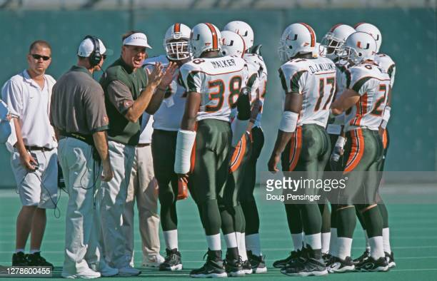 Butch Davis, Head Coach for the University of Miami Hurricanes talks to his offensive line in the huddle during the NCAA Big East Conference college...