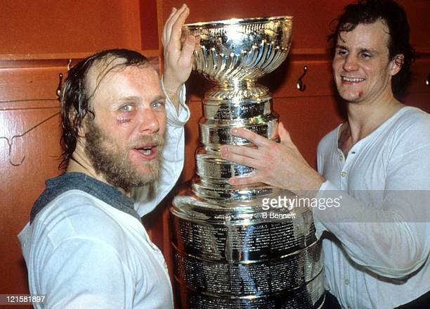 Butch Goring and Stefan Persson of the New York Islanders celebrate with the Stanley Cup Trophy in the locker room after the Islanders defeated the...