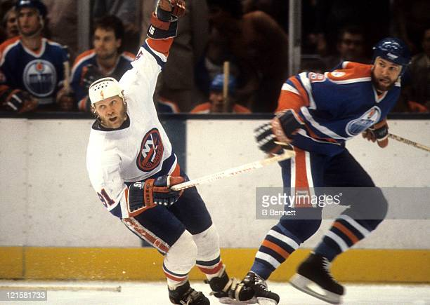 Butch Goring of the New York Islanders and Don Jackson of the Edmonton Oilers skate on the ice during the 1983 Stanley Cup Finals in May, 1983 at the...
