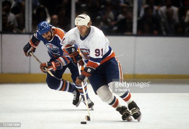 Butch Goring of the New York Islanders skates with the puck as Charlie Huddy of the Edmonton Oilers follows behind during the 1983 Stanley Cup Finals...