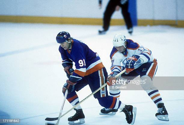 Butch Goring of the New York Islanders skates with the puck as Jari Kurri of the Edmonton Oilers defends during the 1984 Stanley Cup Finals in May...
