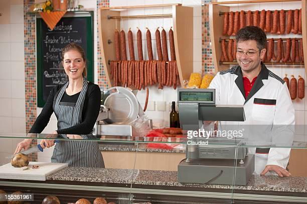 Butcher y hembra ejecutivo de ventas detrás de contador
