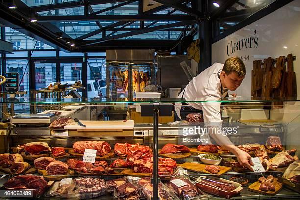 A butcher arranges fresh meat for sale at a market stall inside the TorvehallerrneKBH marketplace in Copenhagen Denmark on Sunday Jan 19 2014 Denmark...