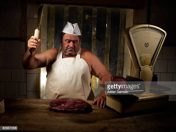 Butcher chopping meat at counter