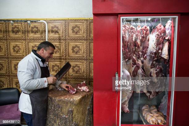 A butcher chops meat at a store in Baku Azerbaijan on Friday March 17 2018 Azerbaijan's economy barely returned to growth last year increasing 01...