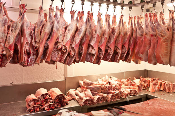 Butcher cuts and processes meat in a London Market