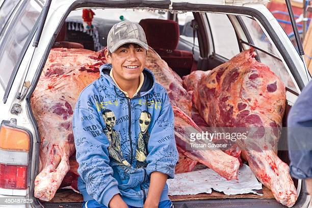 Butcher delivering beef carcass to meat market in Uyuni . How many cows can you fit in a car? At least one, if you cut it in quarters. Other...