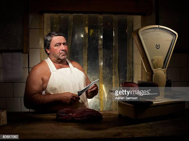 Butcher feeling sharpness of knife with thumb