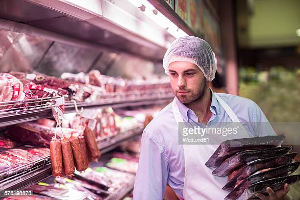 Butcher filling shelf with packaged meat