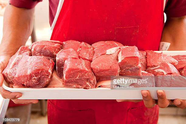 Butcher holding fresh cut meat on tray