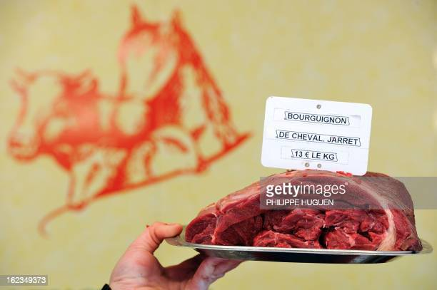 A butcher holds a piece of horse meat at a horse butchery in Anzin northern France on February 22 2013 AFP PHOTO PHILIPPE HUGUEN