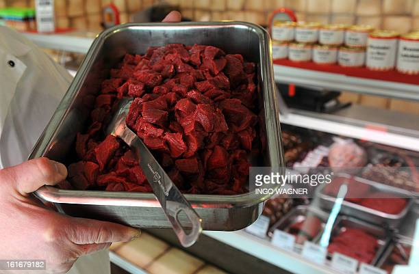 A butcher holds a tray of horse meat on sale at his shop in Bremen northern Germany on February 14 2013 scandal over horsemeattainted food spiralled...