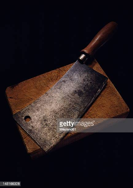 Butcher knife with chopping board on black background
